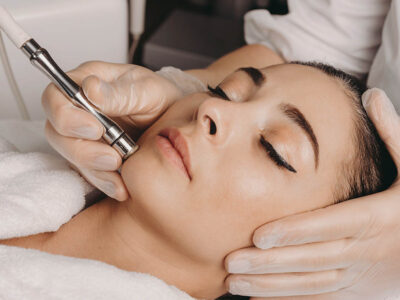 Brunette caucasian woman having a spa procedure for the skin of her face done with an apparatus by a spa worker